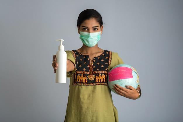 Portret młoda dziewczyna używa lub odkażający żel od butelki dla ręk czyści światową kulę ziemską z maską lub trzyma.
