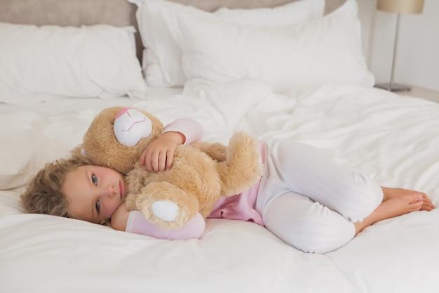 Portret młoda dziewczyna z faszerującym zabawkarskim odpoczywać w łóżku w domu