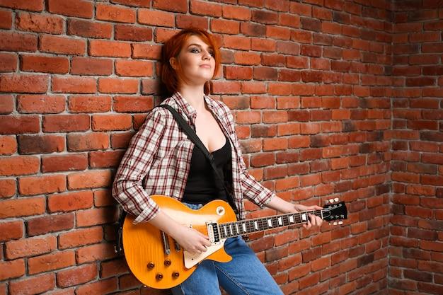 Portret młoda dziewczyna z gitarą nad ceglanym tłem.