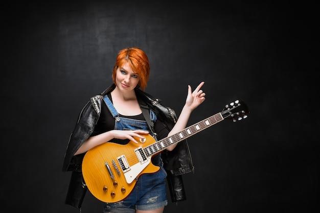Portret młoda dziewczyna z gitarą nad czarnym tłem.
