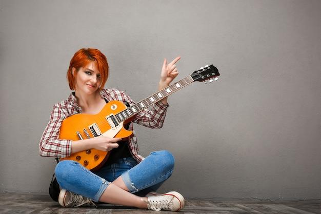 Portret młoda dziewczyna z gitarą nad szarym tłem.