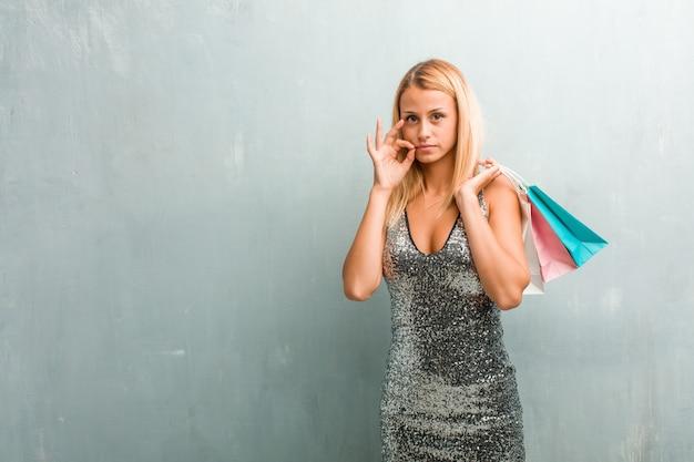 Portret młoda elegancka blondynki kobieta utrzymuje sekret lub pyta dla ciszy. trzymając torbę na zakupy.