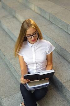 Portret młoda gir dziewczyny studencki obsiadanie na schodkach