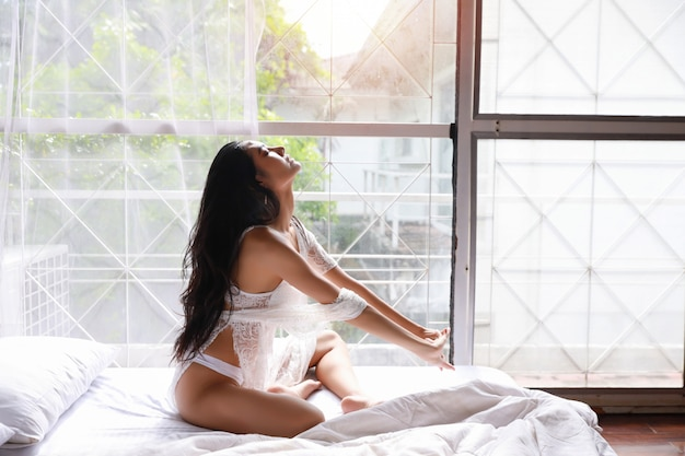 Portret młoda i piękna azjatykcia kobieta jest ubranym białego bielizny bielizna nocna rozciąga w sypialni. młodej ślicznej kobiety długie włosy obsiadanie na łóżku i budzeniu póżno. koncepcja stylu życia