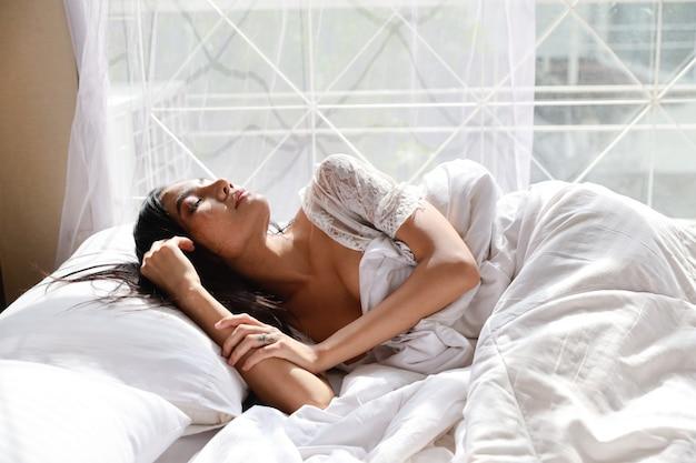 Portret młoda i piękna azjatykcia kobieta jest ubranym białego bielizny bielizna nocna śpi w sypialni. młoda kobieta słodkie długie włosy, leżąc na łóżku i obudź się późno. koncepcja stylu życia