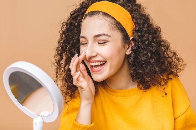 Portret młoda kędzierzawa kobieta używa skóry śmietankę dalej w lustrze odizolowywającym nad beżowym tłem. koncepcja pielęgnacji skóry.