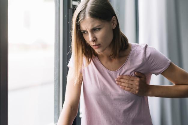 Portret młoda kobieta dotyka jej klatkę piersiową w bólu