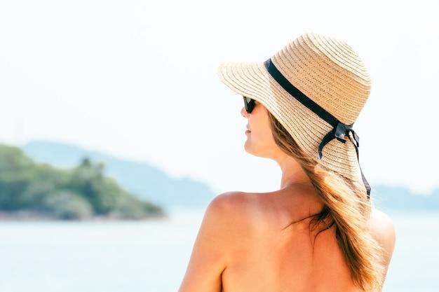 Portret młoda kobieta jest ubranym słomianego kapelusz na plaży