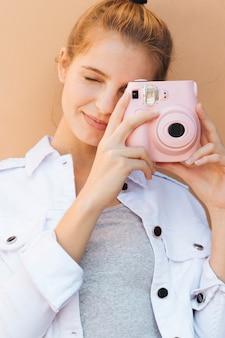 Portret młoda kobieta klika obrazek z różową natychmiastową kamerą przeciw beżowemu tłu