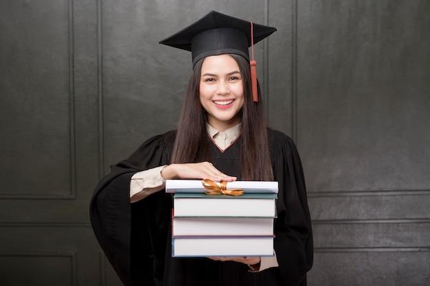 Portret młoda kobieta ono uśmiecha się i rozwesela na czarnym tle w skalowanie todze