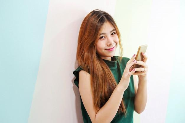 Portret młoda kobieta ono uśmiecha się podczas gdy używać mądrze telefon przy ścianą