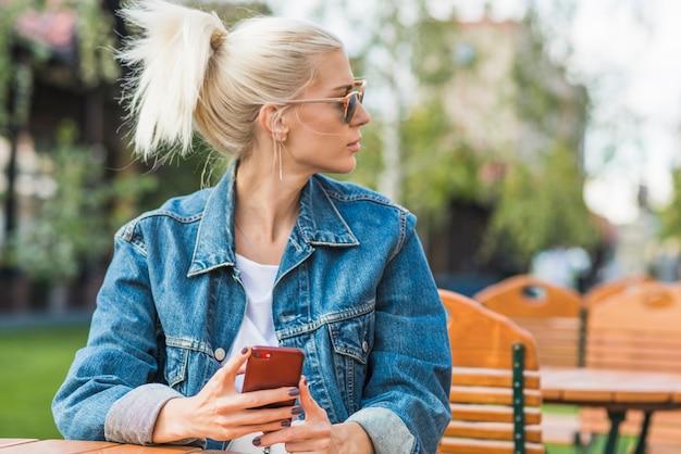 Portret młoda kobieta patrzeje daleko od z telefonem komórkowym