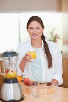 Portret młoda kobieta pije świeże owoc sok