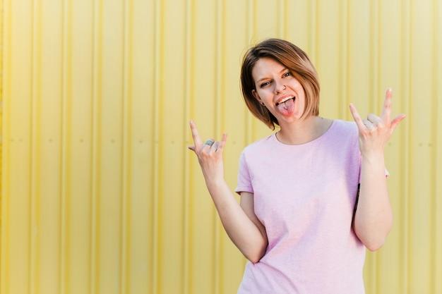 Portret młoda kobieta pokazuje rockowego znaka i przebijającego jęzor