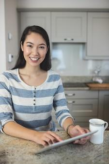 Portret młoda kobieta używa cyfrową pastylkę w kuchni