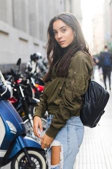 Portret młoda kobieta w czarnej plecak pozyci na ulicznej patrzeje kamerze