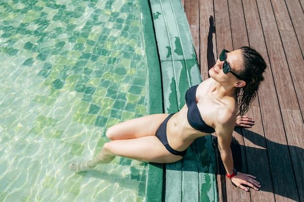 Portret młoda kobieta w swimsuit przy poolside