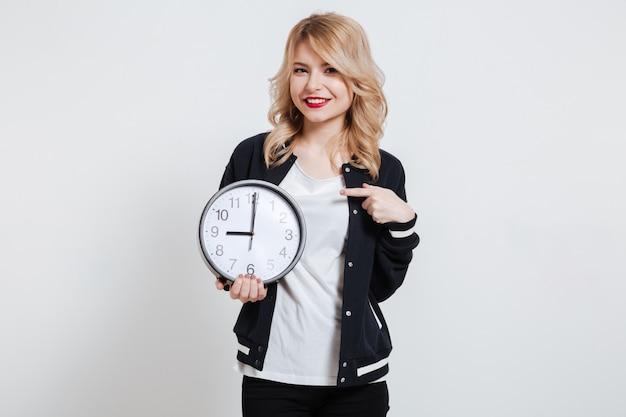 Portret młoda kobieta wskazuje palec na ściennym zegarze