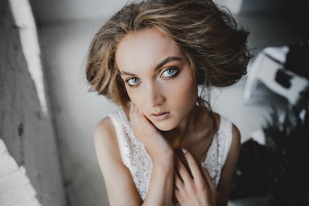 Portret młoda kobieta z głębokimi niebieskimi oczami stoi w pokoju