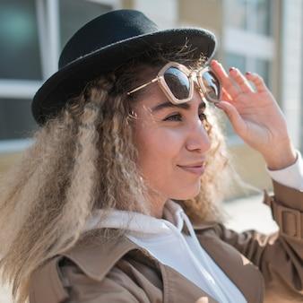Portret młoda kobieta z kapeluszem i okularami przeciwsłonecznymi