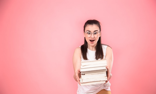 Portret młoda kobieta z szkłami na różowym tle z książkami w ona ręki.