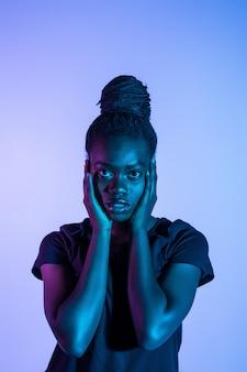 Portret młoda ładna afrykańska kobieta possing w neonowego światła przestrzeni.
