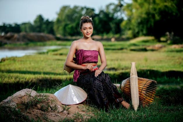 Portret młoda ładna azjatycka kobieta w pięknych tajskich tradycyjnych strojach na polu ryżowym, siedzi w pobliżu sprzętu wędkarskiego