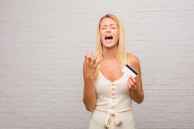 Portret młoda ładna blondynki kobieta przeciw cegły ścianie bardzo okaleczał i przestraszony