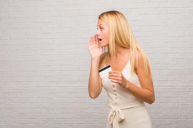 Portret młoda ładna blondynki kobieta przeciw cegły ścianie szepcze plotki półgłosem