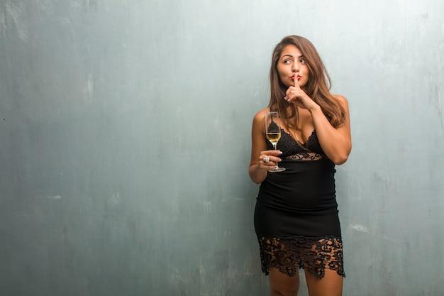 Portret młoda ładna kobieta jest ubranym suknię przeciw ścianie utrzymuje sekret lub pytać dla ciszy