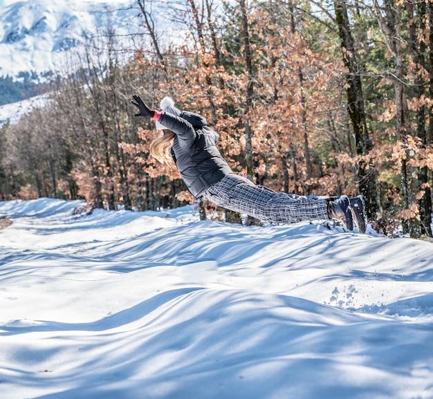 Portret młoda ładna kobieta skoki w śniegu na drodze w zimie