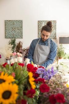 Portret młoda męska kwiaciarnia w fartuchu bierze opiekę piękni kwiaty