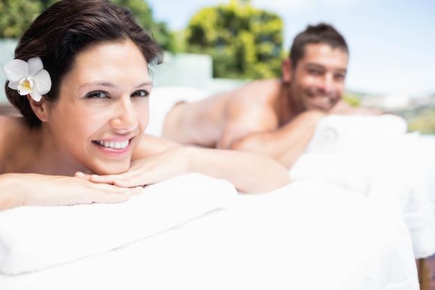 Portret młoda para uśmiecha się i relaks na stole do masażu w spa