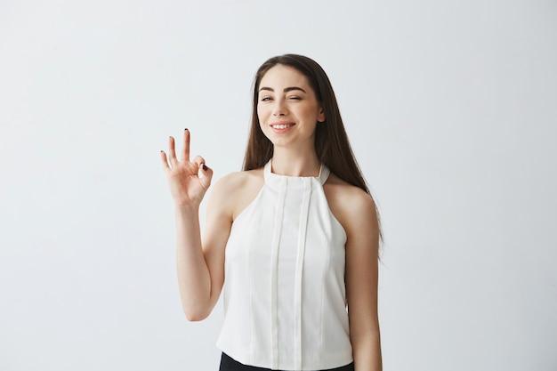 Portret młoda piękna czuła dziewczyna mruga uśmiecha się pokazywać ok.