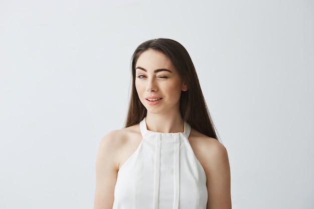 Portret młoda piękna czuła dziewczyna mruga uśmiecha się w bluzce.