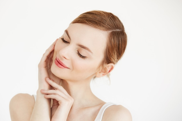 Portret młoda piękna dziewczyna ono uśmiecha się z zamkniętymi oczami dotyka twarz. zabieg na twarz. kosmetyki kosmetyczne i pielęgnacja skóry.