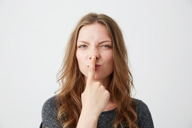 Portret młoda piękna dziewczyna robi śmiesznej twarzy dotyka jej nos.