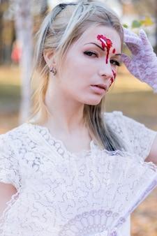 Portret młoda piękna dziewczyna z krwionośnym halloween makijażem na jej twarzy