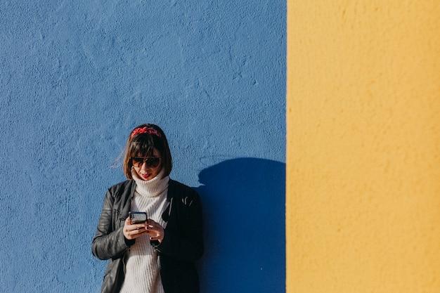 Portret młoda piękna kobieta outdoors używa telefon komórkowego nad błękitnym i żółtym tłem