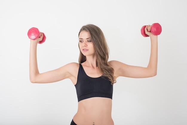Portret młoda piękna kobieta robi ćwiczeniom fizycznym z dumbbells