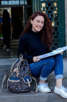 Portret młoda piękna kobieta stoi uśmiechniętego mienia książka na miasto ulicie.