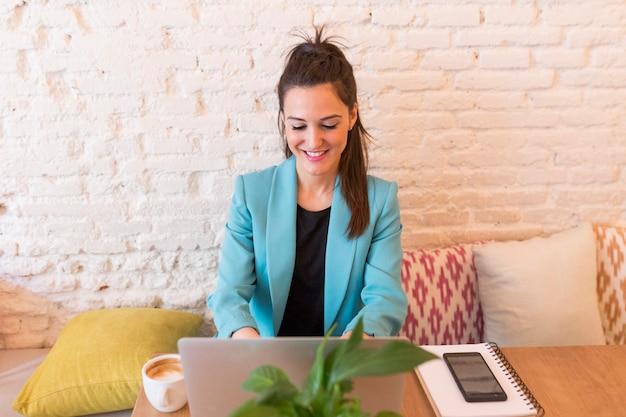 Portret młoda piękna kobieta używa komputerowego laptop w restauraci. ona się uśmiecha. współczesne życie blogera z telefonem komórkowym, tabletem, notatnikiem i kawą na stole. zwykłe ubrania. styl życia