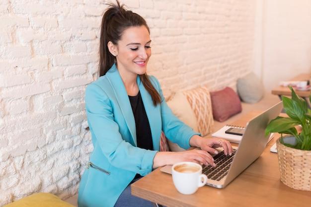 Portret młoda piękna kobieta używa telefon komórkowego w restauraci. ona się uśmiecha. współczesne życie blogera z komputerowym laptopem, tabletem, notatnikiem i kawą na stole. zwykłe ubrania. styl życia