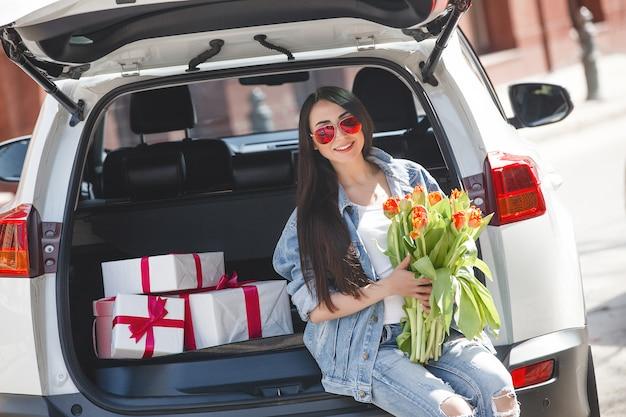 Portret młoda piękna kobieta w wiośnie trzyma bukiet świezi kwiaty.