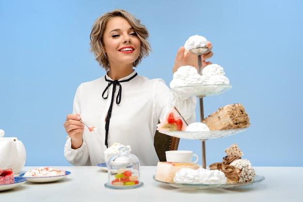 Portret młoda piękna kobieta z cukierkami nad błękit ścianą