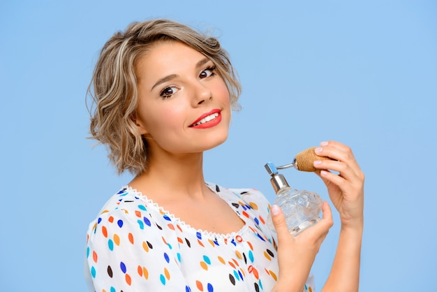Portret młoda piękna kobieta z perfumami nad błękit ścianą