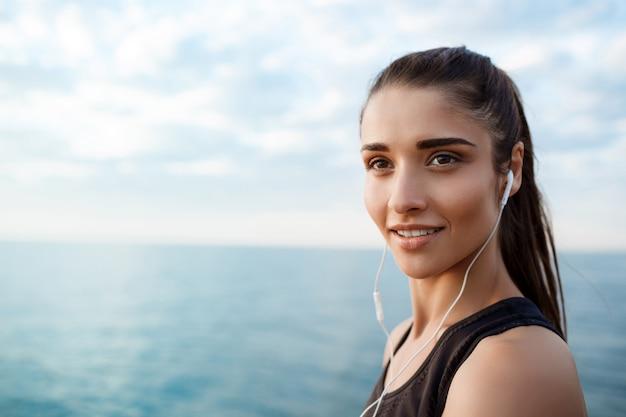 Portret młoda piękna sportive dziewczyna przy wschodem słońca nad nadmorski.