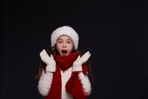 Portret młoda piękna uśmiechnięta dziewczyna w czerwonym santa kapeluszu na ciemnym tle