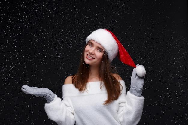 Portret młoda piękna uśmiechnięta dziewczyna w czerwonym santa kapeluszu z białymi płatkami śniegu