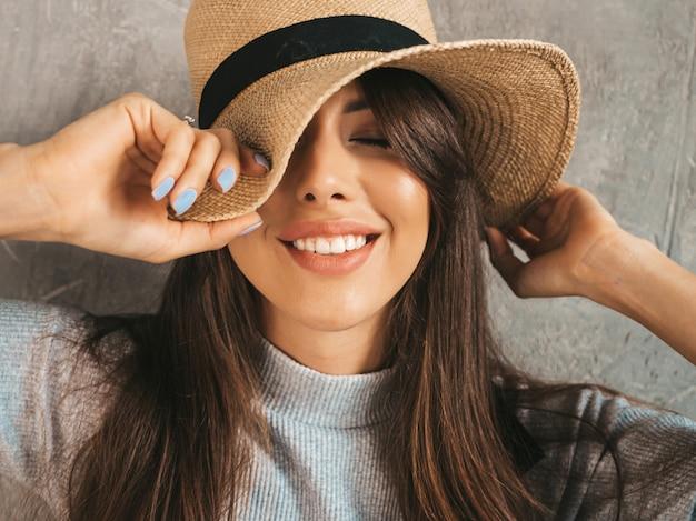 Portret młoda piękna uśmiechnięta kobieta z zamkniętymi oczami. modna dziewczyna w letnie ubrania na co dzień. dotykam jej kapelusza.